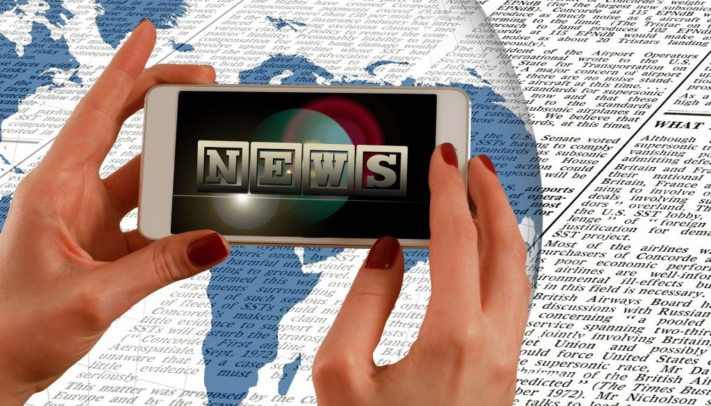 Hands holding mobile phone saying news